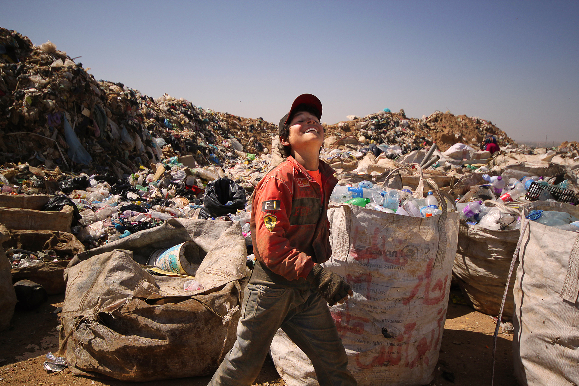 Young Syrian refugee buy working at Jordan's Al-Elhysniat Landfill-Site, near the Syrian border. His F1 jacket belies the terrible working conditions and intense 40 degree heat.