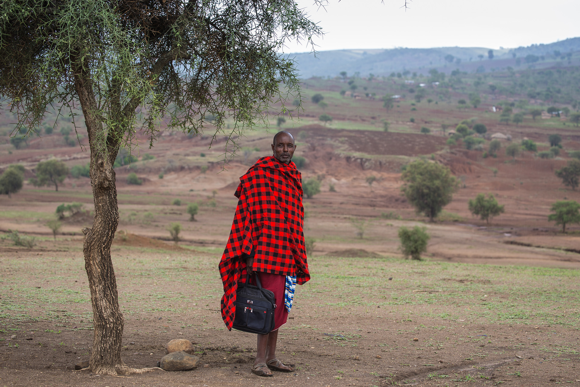 This photograph shows a Maasai pastoralist standing for a portrait with his briefcase following our interview. He works with his cattle in the fields behind him, which show deep trenches falling away from the land caused by soil erosion. 'Five years has shown extreme changes' he informs me sadly.