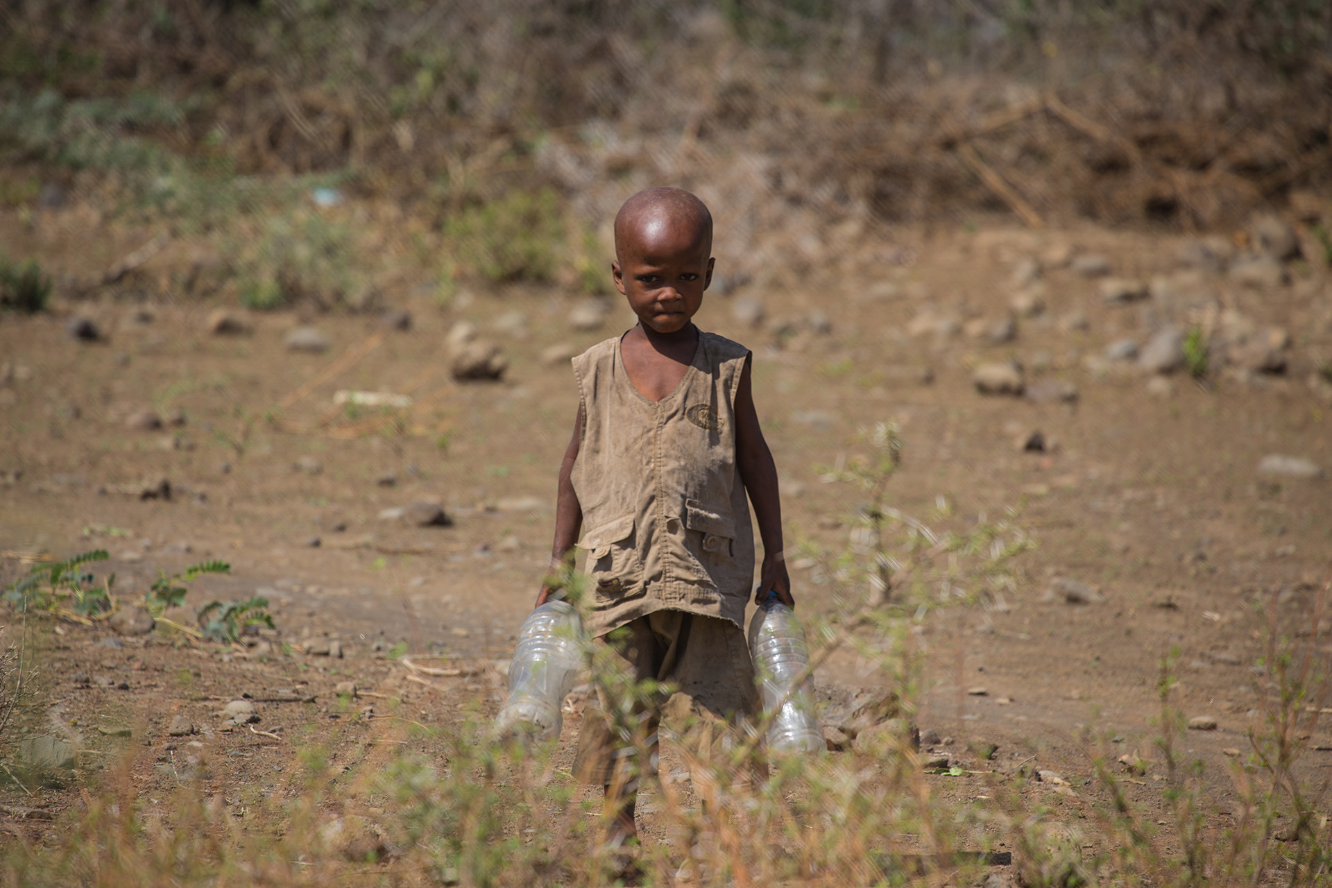 This very young boy couldn't have been more than four years old. He had been sent by his parents to collect water from the bottom of the village. Like many Maasai, they were extremely adverse to have their photograph taken; they do not like it! His expression shows this rather too well.