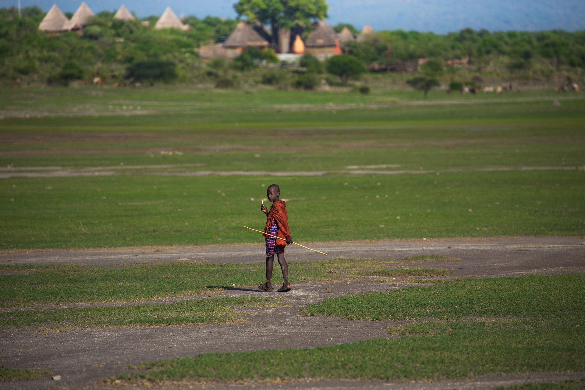 It is said that once they take these responsibilities, they must be mindful of the perils of them. Wearing red and carrying sticks certainly help to ease the mind – as the Maasai believe it discourages lions. In the huge expanse of this open land, a dried-up lake basin, these children must feel vunerable.