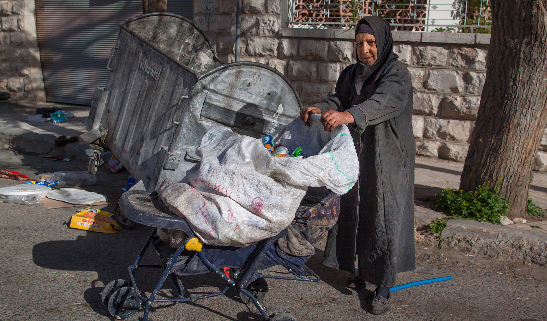 I photographed this very early one morning in Amman's suburbs. She is an itinerant street collector, and therefore unofficial. She rifles through the bins looking for old tin cans for which she was will receive a few cents each.