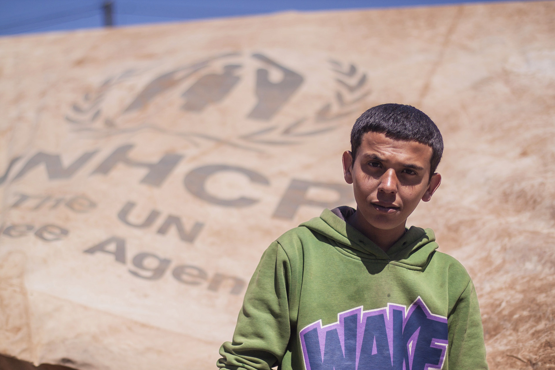 This young lad of 13, a Palestinian refugee, who works by trading recycled goods on the outskirts of Amman stands before his tent. His expression of world weariness appear to defy his tender age.