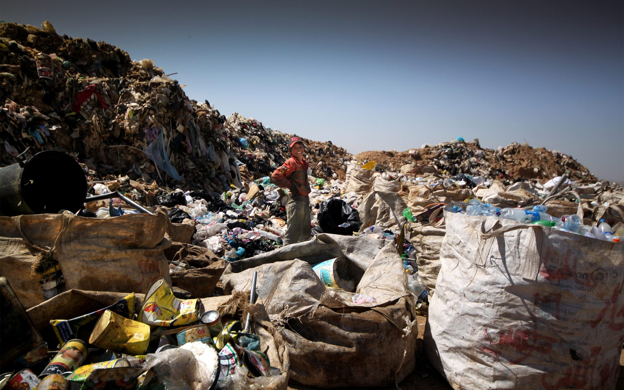 Young Syrian refugee boy working at Jordan's Al Huseyniyat landfill site, near the Syrian border.