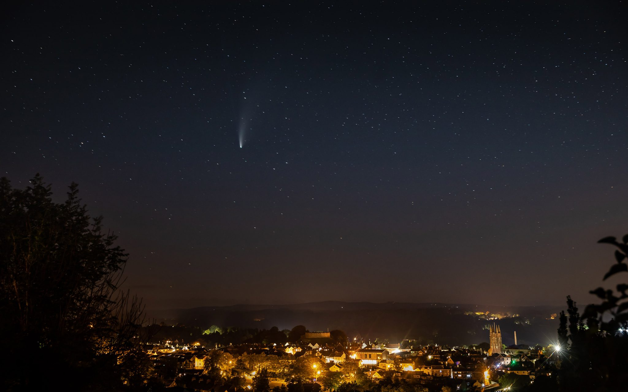 Comet Neowise sets above the 1000-year-old castle in Totnes, South Devon, UK. Dartmoor and Haytor are visible in the distance.